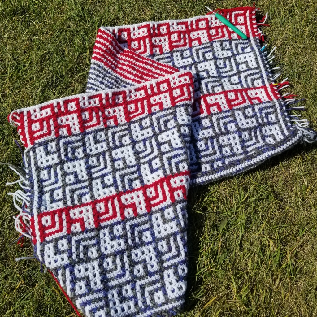 Crochet project using white, red, and blue. Stripes on back, varying squares on the front. Sprawled across the grass.