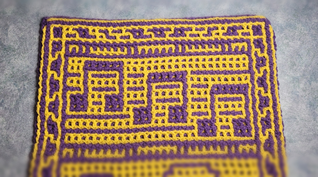 IMAGE: final section of the MusicCAL. Another section of sheet music, then the final border design. Purple and yellow, interlocking crochet.